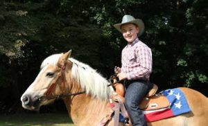 Young boy riding horse with a cowboy hat on.