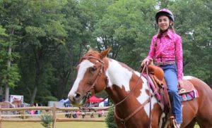 Young girl posing on horse.