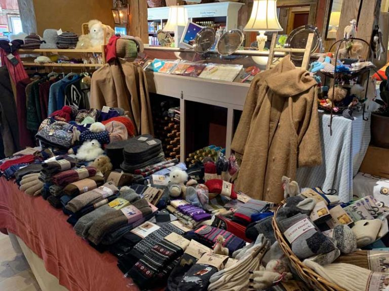 Socks and hat products on a table and coats hanging behind. All made from alpacas wool.