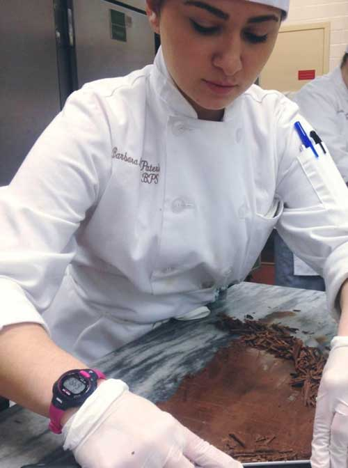 Female chef making brownies in kitchen.